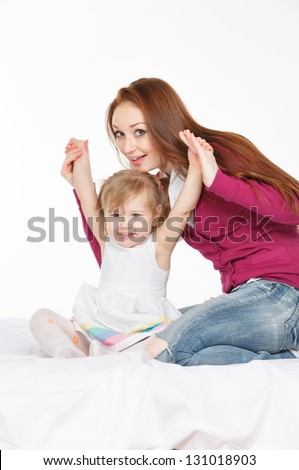 Happy woman and young girl (child) in bed smiling. Mother day concept. - stock photo