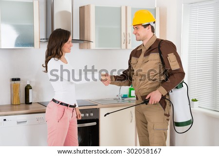 Happy Woman And Young Pest Control Worker Shaking Hands To Each Other In Kitchen Room - stock photo