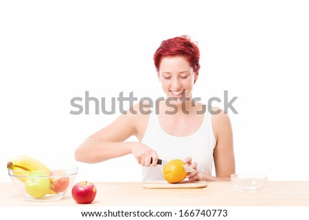happy woman at breakfast cutting a orange on white background - stock photo