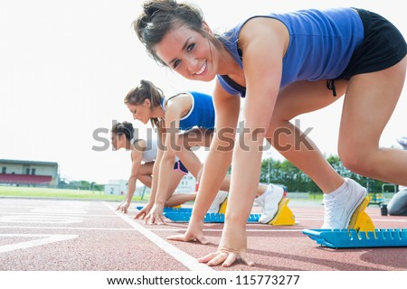 Happy woman at starting blocks on track field - stock photo