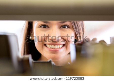 Happy woman at the library looking for a book - stock photo