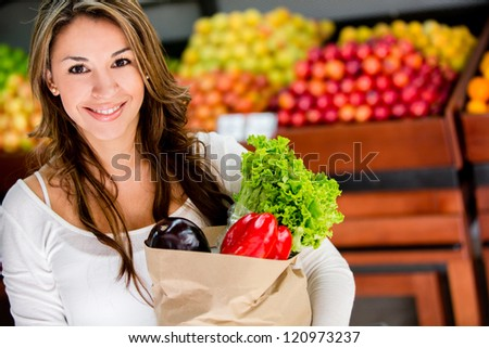 Happy woman at the local market buying groceries - stock photo