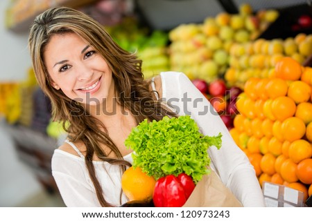 Happy woman at the supermarket buying groceries - stock photo