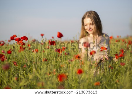 Happy woman at white dress walk between poppies - stock photo
