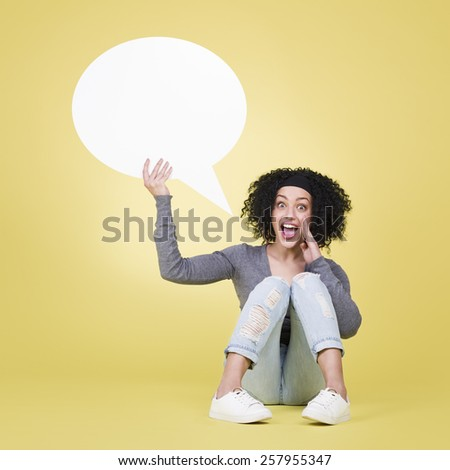 Happy woman being excited holding a white blank sign board with empty copy space, isolated on yellow background. - stock photo