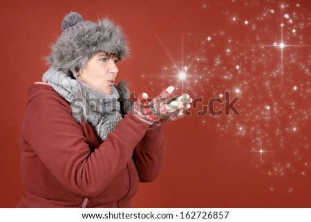 Happy woman blowing stardust in winter season over red background - stock photo
