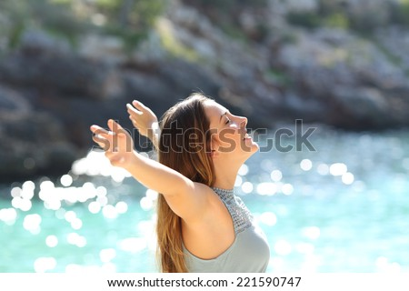 Happy woman breathing fresh air raising arms on holidays with a tropical sea in the background - stock photo