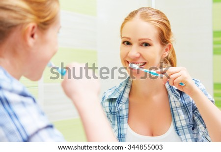 happy woman brushing her teeth with a toothbrush in front of the bathroom mirror - stock photo