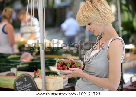 Happy woman buying strawberries at farmer's market - stock photo