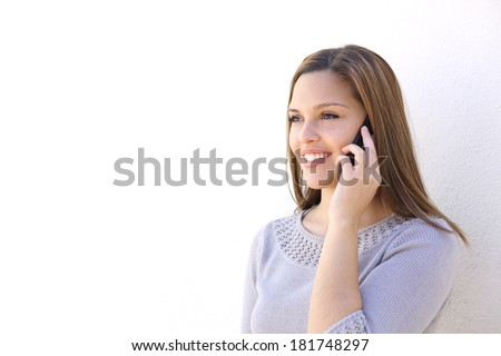 Happy woman calling on the smart phone on a white wall        - stock photo