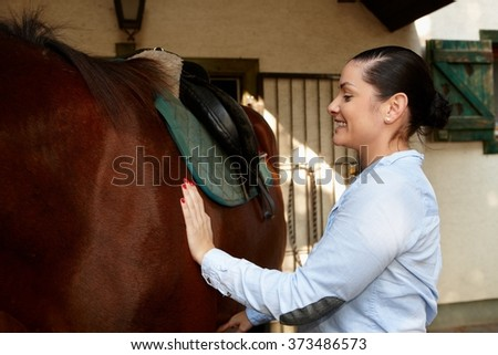 Happy woman caressing brown horse. - stock photo