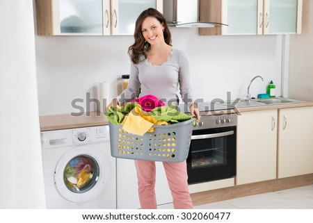 Happy Woman Carrying Laundry Basket In Kitchen Room - stock photo