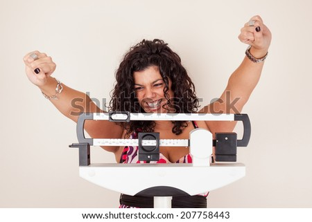 Happy woman celebrating her weight loss on a medical weight scale. - stock photo