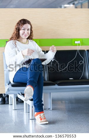 Happy woman charging her electronic devices in place to charge - stock photo