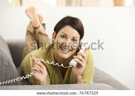 Happy woman chatting on phone, lying on sofa, smiling.? - stock photo