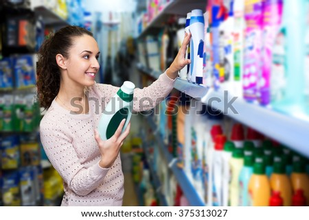 Happy woman choosing detergent in laundry section of supermarket - stock photo