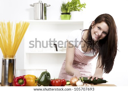 happy woman chopping cucumber for her salad - stock photo