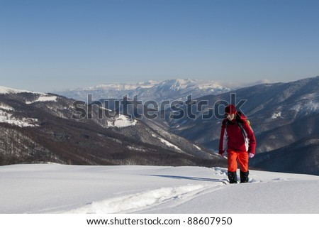 Happy woman climbing mountains in winter with beautiful lanscape behind - stock photo