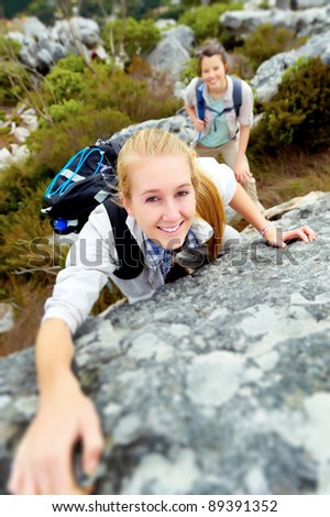 happy woman climbs a rock while trekking outdoors. carefree backpacker smiling at camera - stock photo