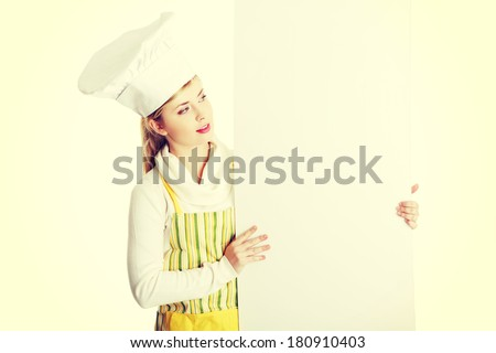 Happy woman cook or baker looking over paper sign billboard.  - stock photo
