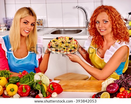 Happy woman cooking vegeterian pizza at home kitchen. - stock photo