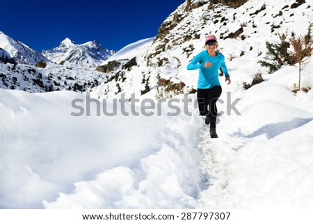 Happy woman cross country trail running in beautiful inspiring mountains landscape. Healthy lifestyle, fitness and exercising outdoors in winter nature. Inspiration and motivation fit and be healthy. - stock photo