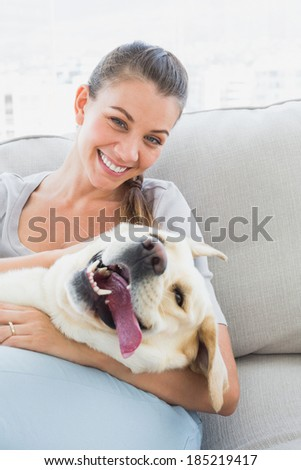 Happy woman cuddling her yellow labrador on the couch at home in the living room - stock photo