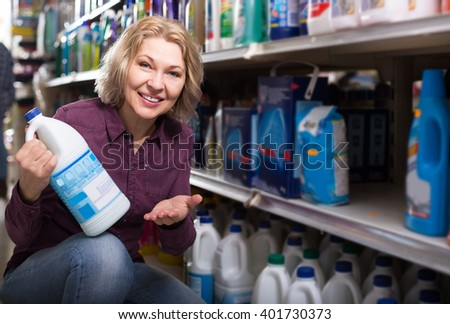 happy woman customer buying detergents for laundry in shopping mall - stock photo