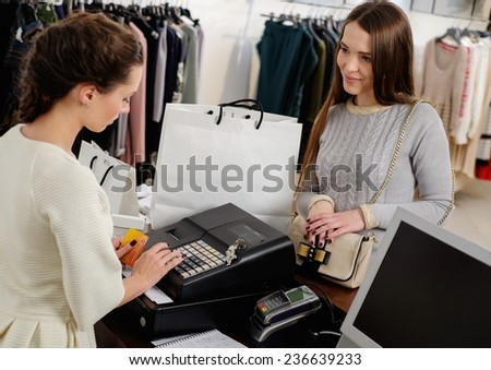 Happy woman customer paying with credit card in fashion showroom - stock photo