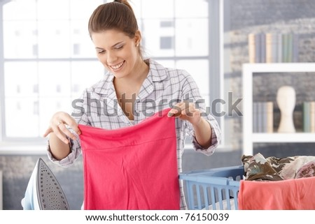 Happy woman doing laundry at home, holding clothes, smiling.? - stock photo