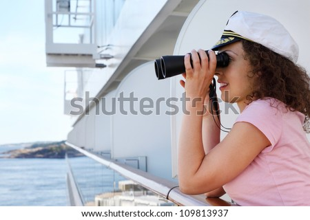 happy woman dressed in cap stands on ship board and looks through binoculars - stock photo