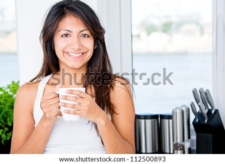 Happy woman drinking coffee in the kitchen - stock photo
