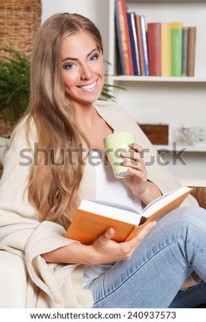 Happy woman drinking tea while reading - stock photo