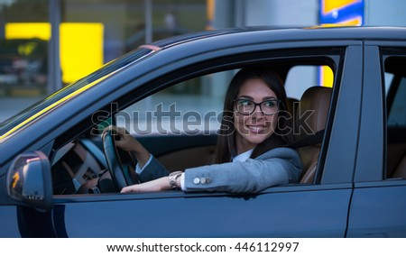 Happy woman driving her new car. High ISO, grainy image. - stock photo