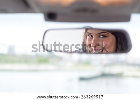 Happy woman driving - reflex in the mirror - stock photo