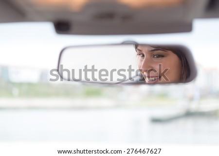 Happy woman driving - reflex in the mirror - stock photo