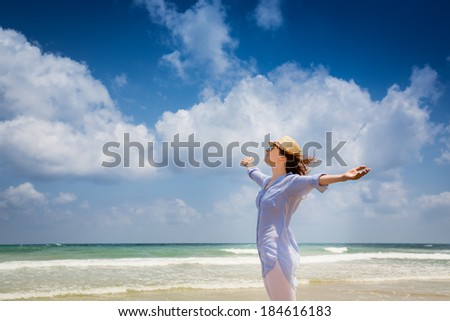 Happy woman enjoying at the beach. Summer vacations concept - stock photo