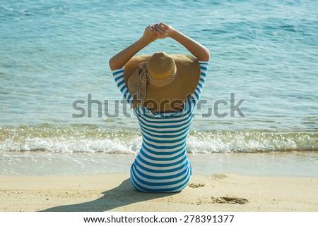 Happy woman enjoying beach relaxing joyful in summer by tropical blue water. Beautiful model happy on travel wearing beach sun hat on Samui beach, Thailand - stock photo