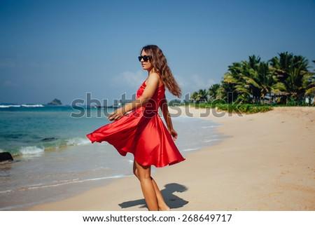 Happy woman enjoying beach relaxing joyful in summer by tropical blue water. Beautiful red dress model happy on travel wearing beach sun straw hat on sandy beach - stock photo
