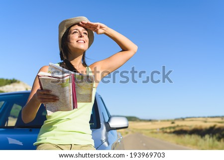 Happy woman enjoying freedom on summer car travel vacation in spain. Female traveler with road map on roadtrip. - stock photo