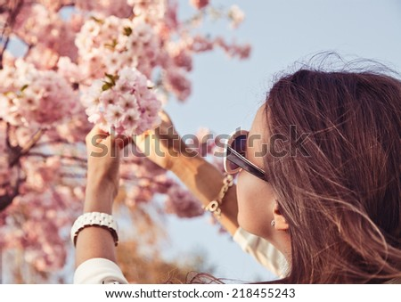 Happy woman enjoying nature. Girl with sakura tree flowers. Focus on face. Spring concept - stock photo