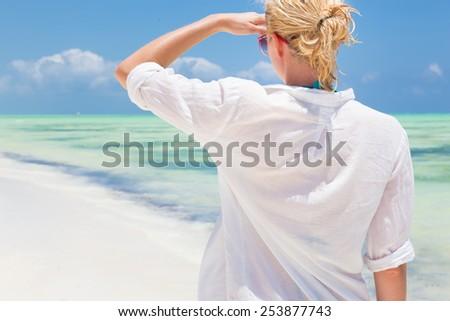 Happy woman enjoying, relaxing joyfully in summer by tropical blue water. Beautiful caucasian model  wearing white beach tunic on vacations looking down picture perfect Paje beach, Zanzibar, Tanzania. - stock photo