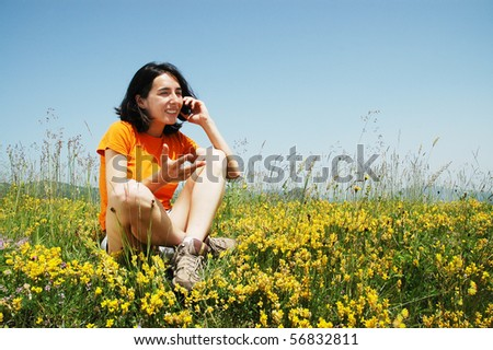 Happy woman enjoying the outdoors using her cell phone - stock photo