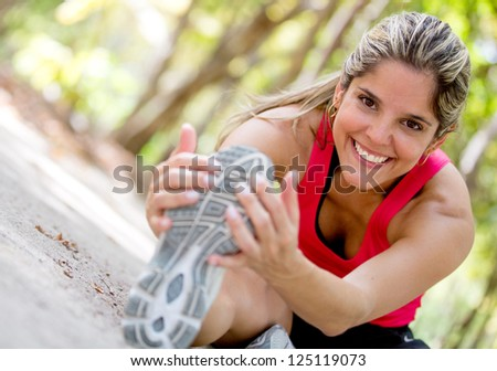 Happy woman exercising at the park and stretching - stock photo