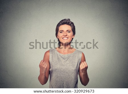 happy woman exults pumping fists ecstatic celebrates success isolated on gray wall background - stock photo