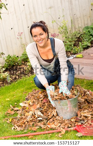 Happy woman filling bucket fall leaves gardening housework rake - stock photo