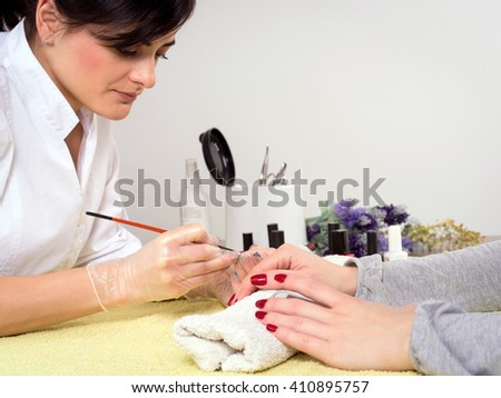Happy woman getting her nails done at the beauty salon - stock photo