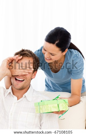 Happy woman giving a present to his boyfriend while hiding his eyes at home - stock photo