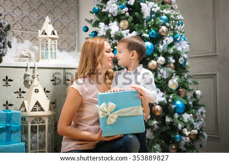 Happy woman giving Christmas present to her son - stock photo