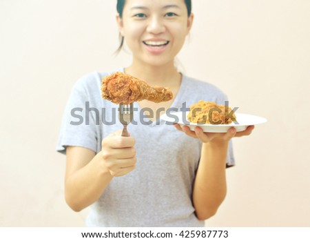 Happy woman giving fried chicken in white plate  - stock photo